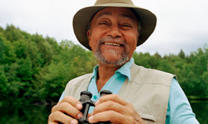 A smiling older man outside holding binoculars