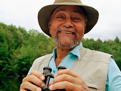A smiling older man outside holding binoculars