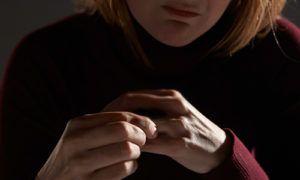 A worried woman holds her ring finger- she's been through a divorce.