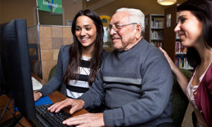 An older man and his two granddaughters use the computer in a library