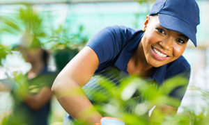 A smiling woman gardens in a nursery store