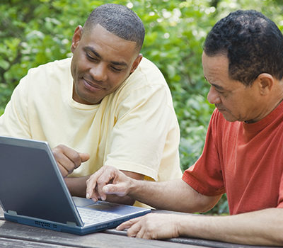 Two men use a laptop computer
