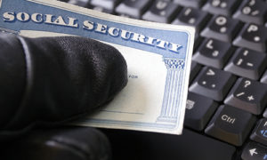 An identity thief holds a Social Security card in front of a keyboard