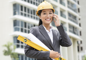 A single working woman is holding blueprints at a construction site while talking on the phone.