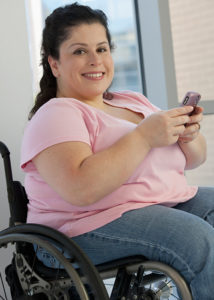 Woman in wheelchair smiling using smartphone