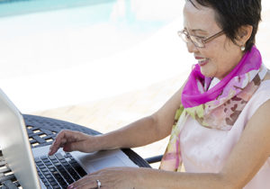 A woman sits at her computer on the beach