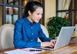 A young woman uses the computer.
