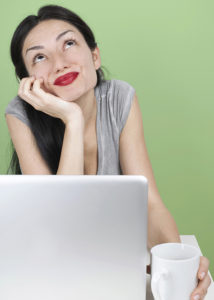 A woman thinks while using the computer