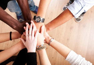 A group of diverse people join hands in cooperation.