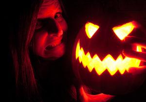 woman holding a light jack-o-lantern