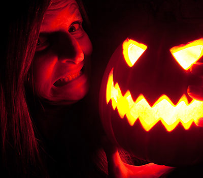 A woman smiling while hodling a jack-o-lantern near her face.