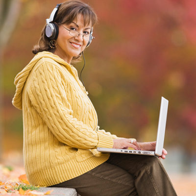 happy woman outside with laptop