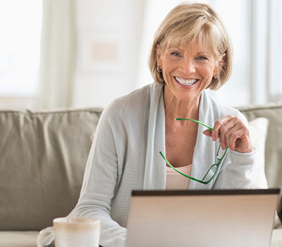 A woman smiling towards you while using a laptop.
