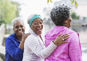 A group of three happy, senior African American women standing together at the park. Two of them are looking at the camera and laughing. The main focus is on the woman in the middle.