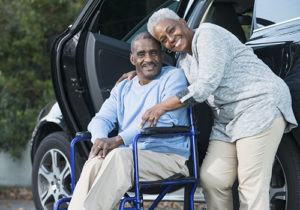 A happy senior African American couple outside a car. The man is sitting in a wheelchair and his wife is standing beside him with her arm around his shoulder.