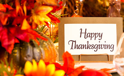 Happy Thanksgiving Text on a card surrounded by Thanksgiving decorations