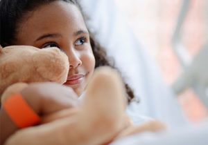 little girl smiling, holding teddy bear