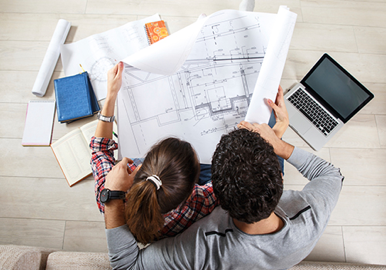 photograph of a couple looking at the blueprint of a house, planning for their future.
