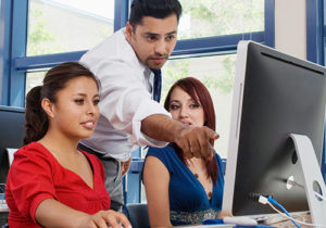 A photograph of a mentor educating two students in front of a computer monitor.