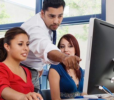 A man pointing out to two women something on a computer screen.
