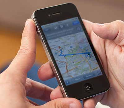 A pair of hands holding an iPhone that displays a map.