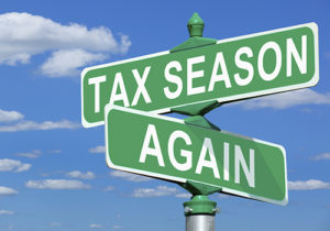 a picture of stree signs that read tax season, and again.