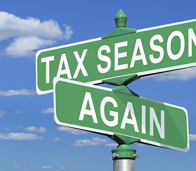 A picture of street signs that read tax season, and again.
