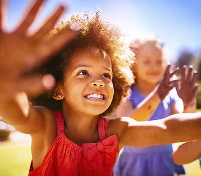 Happy little girl smiling and holding up her hands joyfully in the sun