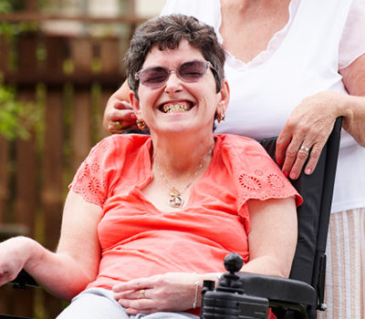 A disabled woman in a wheelchair with her care mother in garden