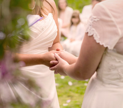 Bride holding hands with her bridesmaid.
