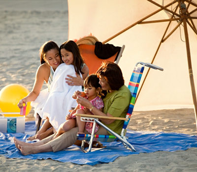 A women holding their daughters at the beach.