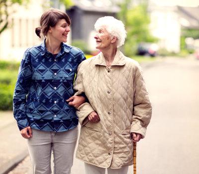 A woman walking with elderly woman