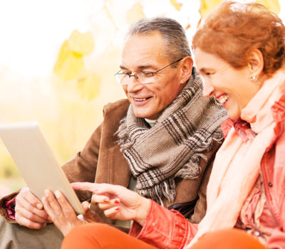 An elderly couple using a tablet in a park