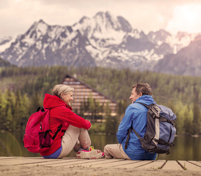 A man and woman with backpacks, looking at a mountain