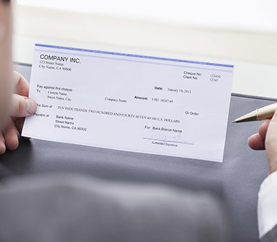 A close-up of a businessman filling blank cheque