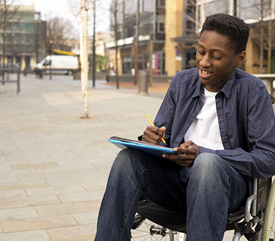 A young man in a wheelchair writing a letter