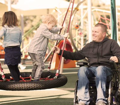 A man in wheelchair pushing kids on a tire swing