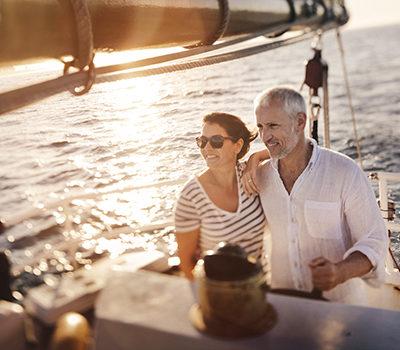 A senior active couple enjoying the fresh ocean breeze on their leasure cruise on their yacht