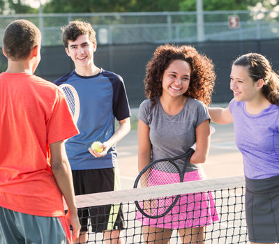 Two boys and two girls playing tennis together