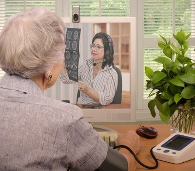 An elderly woman using a blood pressure machine while on a on video conference with a doctor