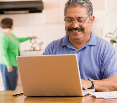 A smiling man using a laptop