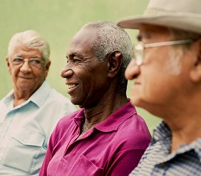 Three elderly men sitting together while smiling