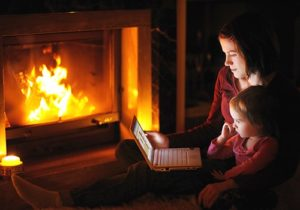 mother and daughter on computer by fireplace