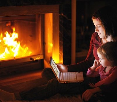 A mother and daughter watching a video on a laptop by fireplace