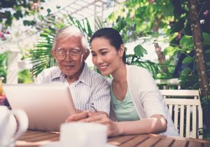 woman and elderly man on laptop
