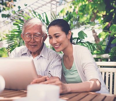 A woman and elderly man on laptop