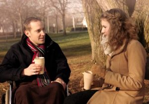 man and woman drinking coffee outside