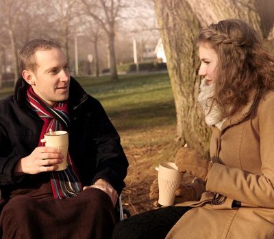 A man and woman drinking coffee and sitting together outside