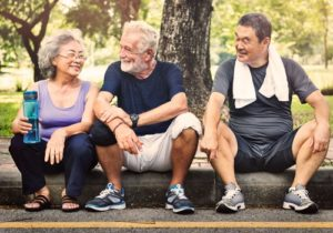 3 elderly people siting on a stoop