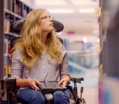 A woman in a wheelchair inside of a library